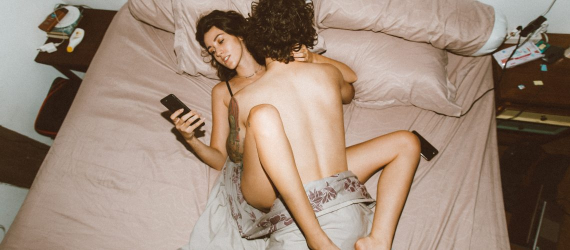 couple-having-sex-and-using-smartphone-4553619